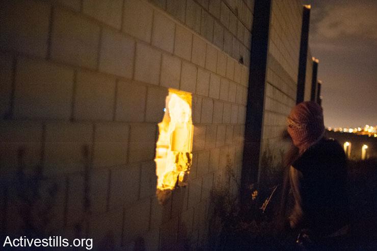 פעילים פלסטינים פוערים חור בחומת ההפרדה (צילום: אקטיבסטילס)
