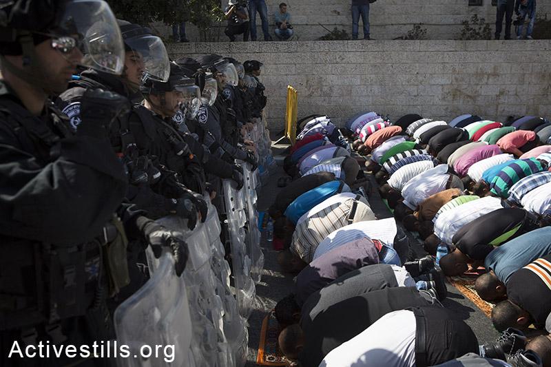 פלסטינים מתפללים לכיוון אל-אקסה תחת שמירה של כוחות מג״ב במהלך תפילת יום השישי, בשכונת ואדי אל-ג׳וז, מזרח ירושלים, 17 אוקטובר, 2014. (אקטיבסטילס)