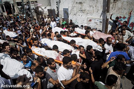 הלווייתם של 21 בני משפחת אלנג'אר שנהרגו זמן קצר לפני הפסקת אש, בכפר בני סוהילא, מזרחית לח'אן יונס, 26 ביולי, 2014. משפחת אלנג'אר ברחה מביתה בחוזעה, כמו רבים אחרים מכפרם, בעקבות כיבוש המקום ע״י הצבא הישראלי. כ-1000 פלסטינים נהרגו עד כה בעזה וכ-5000 נפצעו. (אן פאק/אקטיבסטילס)