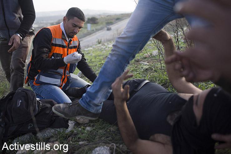 חובשים מטפלים בנער פלסטיני שנפצע מאש חיה, שנורתה על ידי הצבא הישראלי, במהלך עימותים מחוץ הכלא הצבאי עופר, סמוך לעיירה ביתוניא, 27 נובמבר 2015. (אקטיבסטילס)