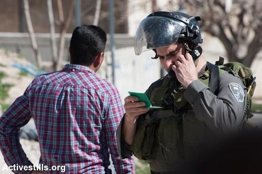 חייל בודק תעודת זהות של פלסטיני. ישראל שולטת ברישום האוכלוסין הפלסטיני ומנפיקה לפלסטינים את תעודות הזהות הירוקות שלהם שמובחנות מאלו התכולות של הישראלים (אקטיבסטילס)