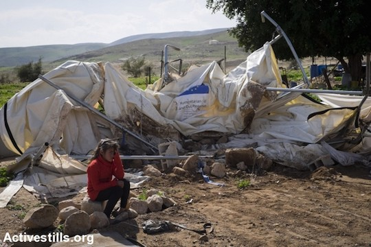 ילדה יושבת על מה שנותר מהמבנה ששימש אותה כבית ונתרם במימון האיחוד האירופי. הכפר פאסאיל, בקעת הירדן, 10 בפברואר 2016. באותו יום ביצע המנהל האזרחי הריסות בארבעה מוקדים בבקעת הירדן. שבע משפחות איבדו את בתיהן ושישה מבנים לחיות נהרסו. 71 בני אדם נותרו ללא קורת גג לראשם. צינורות שסיפקו מים לכ-300 בני אדם ניזוקו. (אורן זיו/אקטיבסטילס).