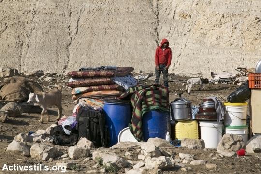 צעיר פלסטיני עומד ליד החפצים שהציל מביתו לאחר הריסת ביתו קרזליה, בקעת הירדן (אקטיבסטילס)