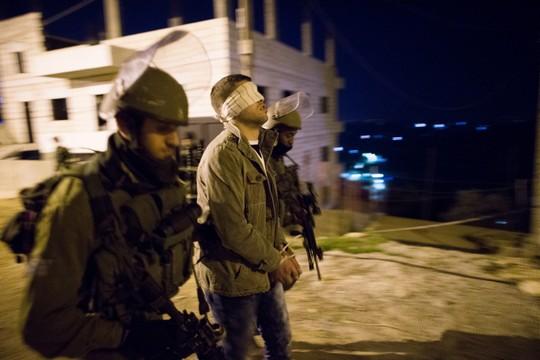 חיילים עוצרים פלסטיני בלילה (נתי שוחט / פלאש90)