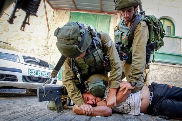 חיילים עוצרים פלסטיני במהלך פשיטות על בתים בחברון (ויסאם השלמון / פלאש90)
