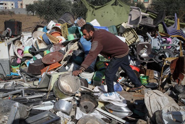 פלסטיני תושב עזה אוסף חפצים מהריסות ביתו שלא שוקמו מאז המלחמה לפני שנתיים. דצמבר 2016 (עבד רחים חטיב / פלא90)