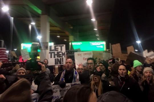 """""""תנו להם להיכנס"""", """"כל בני האדם חוקיים"""". מפגינים בשדה התעופה JFK בניו יורק. (צילום: אמה לואיס/Just Vision)"""