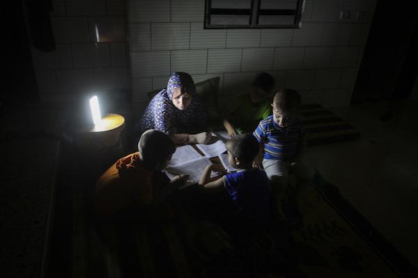 ילדים מכינים שיעורי בית לאור תאורת חירום בהפסקת החשמל הקבועה של עזה. מאי 2016 (עבד רחים חטיב / פלאש90)