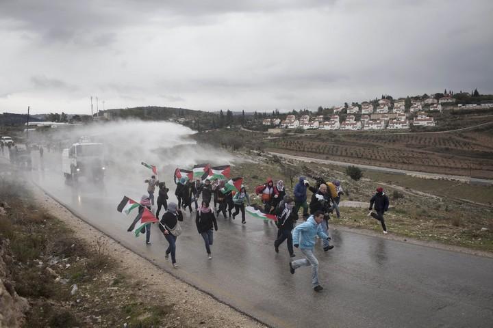 """פעילים פלסטינים, בינלאומיים וישראלים בורחים מרכב """"בואש"""" של הצבא במהלך הפגנה נגד הכיבוש בכפר נבי סאלח בגדה המערבית. 13 בינואר 2012 (אקטיבסטילס)"""