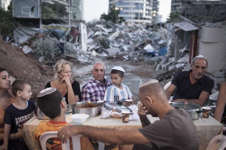 בני משפחת כדורי, אשרם וחמיס יושבים לארוחת ראש השנה על חורבות ביתן ההרוס בשכונת גבעת עמל בתל אביב. 19 בספטמבר, 2104. (שירז גרינבאום/אקטיבסטילס)