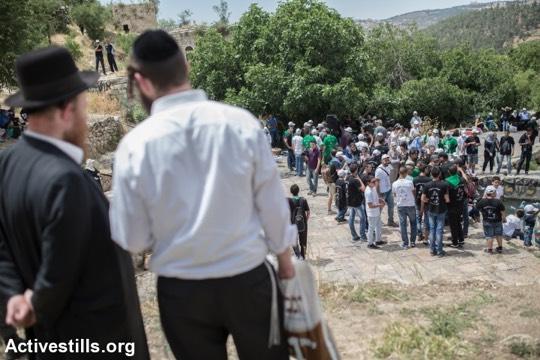 פליטים פלסטינים מהכפר הפלסטיני ״ליפתא״ מנציחים את זכר הנכבה, בעוד יהודים צופים בהם (יותם רונן/אקטיבסטילס)