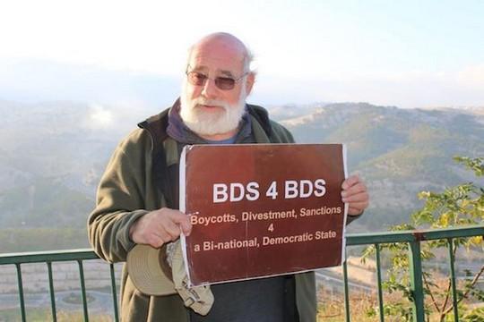 ג'ף הלפר מחזיק בשלט BDS. הלפר לא החזיק את השלט ביום בו עוכב על ידי המשטרה (באדיבות ג'ף הלפר)