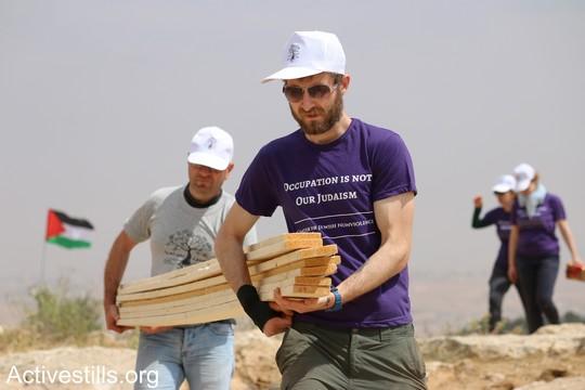 """פעיל פלסטיני ופעיל יהודי אמריקאי נושאים ביחד קורות עץ כדי לבנות את אחד מאוהלי המאחז. """"צומוד, מחנה החירות"""". הכפר סארורה הגדה המערבית, 19 במאי 2017 (צילום: אחמד אל-באז אקטיבסטילס)"""