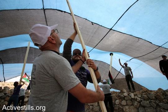 """פעיל פלסטיני ופעיל יהודי אמריקאי מניחים קורות של אוהל. """"צומוד, מחנה החירות"""". הכפר סארורה הגדה המערבית, 19 במאי 2017 (צילום: אחמד אל-באז אקטיבסטילס)"""