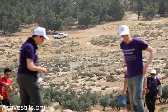 """כוחות בטחון ישראליים צופים בפעילים הבונים את המאחז. """"צומוד, מחנה החירות"""". הכפר סארורה הגדה המערבית, 19 במאי 2017 (צילום: אחמד אל-באז אקטיבסטילס)"""