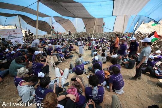 """הפעילים מאזינים להרצאה של אחד מזקני הכפר. """"צומוד, מחנה החירות"""". הכפר סארורה הגדה המערבית, 19 במאי 2017 (צילום: אחמד אל-באז אקטיבסטילס)"""