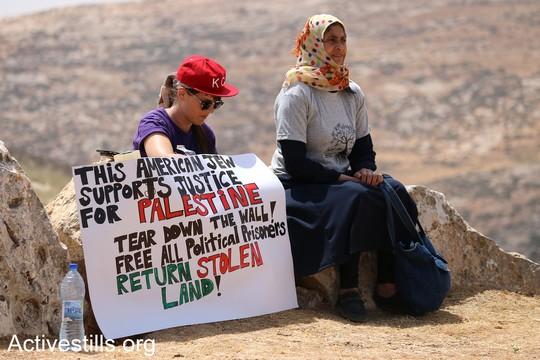 """פעילה יהודיה אמריקאית ואשה פלסטינית יושבים יחד. על השלט שהן אוחזות כתוב """"היהודיה האמריקאית הזאת תומכת בצדק לפלסטין. שברו את החומה, שחררו את כל האסירים הפוליטיים . """"צומוד, מחנה החירות"""". הכפר סארורה הגדה המערבית, 19 במאי 2017 (צילום: אחמד אל-באז אקטיבסטילס)"""