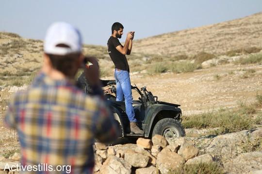 """פעיל ממחנה השלום מצלם מתנחל שהגיע למקום כדי לעורר פרובוקציות. """"צומוד, מחנה החירות"""". הכפר סארורה הגדה המערבית, 19 במאי 2017 (צילום: אחמד אל-באז אקטיבסטילס)"""