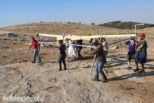 """הפעילים מקימים אוהל חדש במקום האוהל שהחיילים פירקו. """"צומוד, מחנה החירות"""". הכפר סארורה הגדה המערבית, 24 במאי 2017 (צילום: אחמד אל-באז אקטיבסטילס)"""