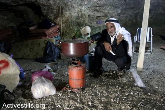 """פאדל אל עאמר, פלסטיני מזקני סארורה, מכין ארוחת ערב במערה שלו ששוקמה על ידי הפעילים. הפעילים הקימו את המאחז בכוונה לסייע לתושבי הכפר לחזור לבתיהם. """"צומוד, מחנה החירות"""". הכפר סארורה הגדה המערבית, 24 במאי 2017 (צילום: אחמד אל-באז אקטיבסטילס)"""