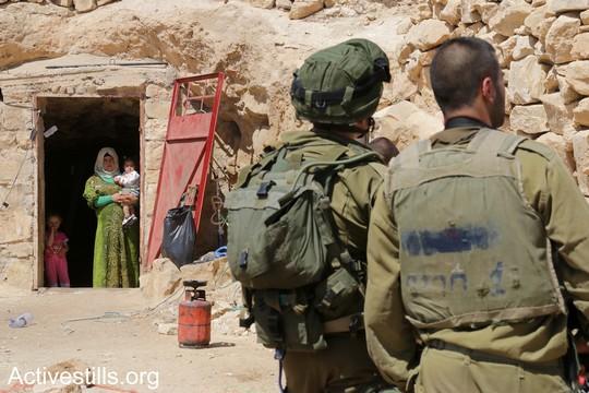 """חיילים בכניסה למערה שמשמשת בית למשפחה מתושבי סארורה, במהלך ניסיון הפינוי השני של המאחז. """"צומוד, מחנה החירות"""". הכפר סארורה הגדה המערבית, 25 במאי 2017 (צילום: אחמד אל-באז אקטיבסטילס)"""