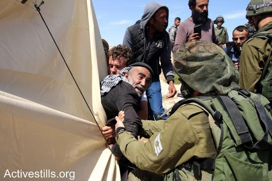 """פלסטיני תושב סארורה מנסה להתנגד לניסיון הפינוי של הצבא. """"צומוד, מחנה החירות"""". הכפר סארורה הגדה המערבית, 25 במאי 2017 (צילום: אחמד אל-באז אקטיבסטילס)"""