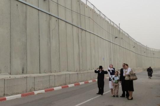 """""""בטוחים"""": מתפללים חרדים מישראל מול קיר הבטון שהחליף את המבנה המוכר בקבר רחל (צילום: יובל בן עמי)"""