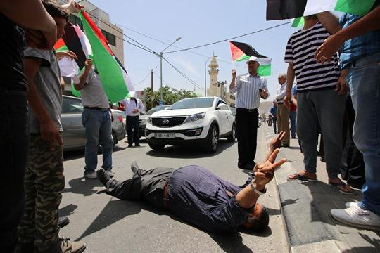 מפגין חוסם את הכביש בהפגנה היום בחווארה (צילום: אחמד אל באז, אקטיבסטילס)