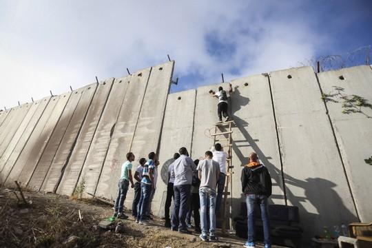 מערכת החינוך משתתפת בבניה של אותן חומות שקיימות במציאות. פלסטינים מנסים לחצות את חומת ההפרדה ליד מחסום קלנדיה (פלאש 90)