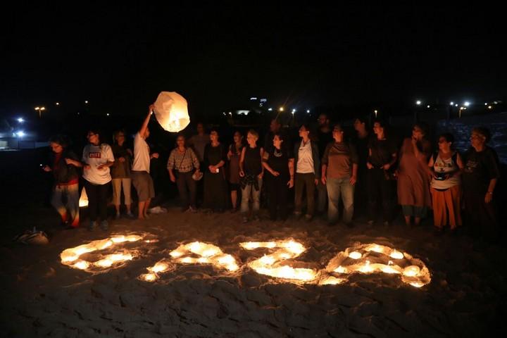 """פעילים יוצרים את הכיתוב """"עזה"""" בסולידריות עם מליוני תושבי הרצועה השרויים בעלטה. חוף אשקלון, 19 ביוני 2017. (צילום: היידי מוטולה/אקטיבסטילס)"""