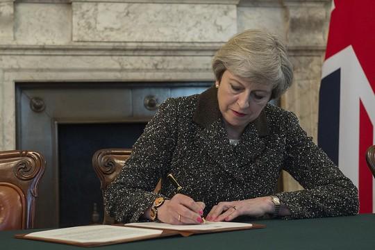 תרזה מיי, ראש ממשלת בריטניה חותמת על מכתב לנשיא המועצה האירופית המודיע על כוונת בריטניה להיפרד מהאיחוד האירופי (צילום: ג'יי אלן/פליקר CC BY-NC-ND 2.0)