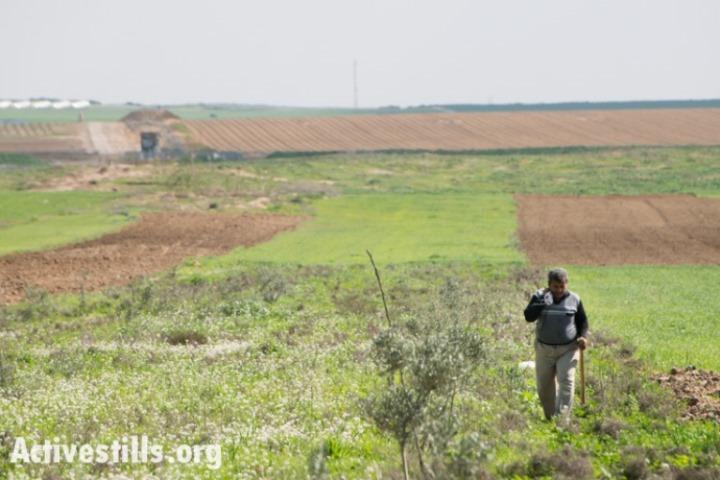 חקלאי פלסטיני עובד בשדות הסמוכים לגבול המזרחי של עזה. עמדות הצבא הישראלי נראות מרחוק בצד שמאל (ראיין רודריק ביילר/אקטיבסטילס)
