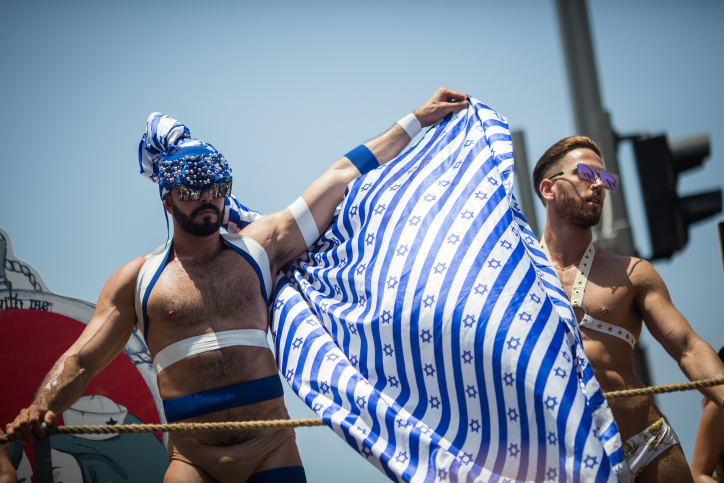"""נאורות מדומה על הגב של להט""""ב פלסטינים. צועדים עטופים בדגלי ישראל במצעד הגאווה בתל אביב , 9 ביוני 2017. (צילום: הדס פרוש, פלאש90)"""