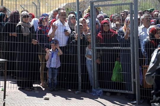 פלסטינים מהגדה המערבית חוצים דרך מחסום בית לחם בדרכם לתפילות יום השישי האחרון של הרמאדן במסגד אל אקצא בירושלים. 23 ביוני 2017 (צילום: אחמד אל-באז/אקטיבסטילס)