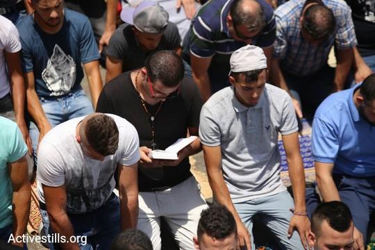 מאמין נוצרי מתפלל בין מאמינים מוסלמים. המחאה איחדה את המזרח ירושלמים. (צילום: פאיז אבו רמלה/אקטיבסטילס)