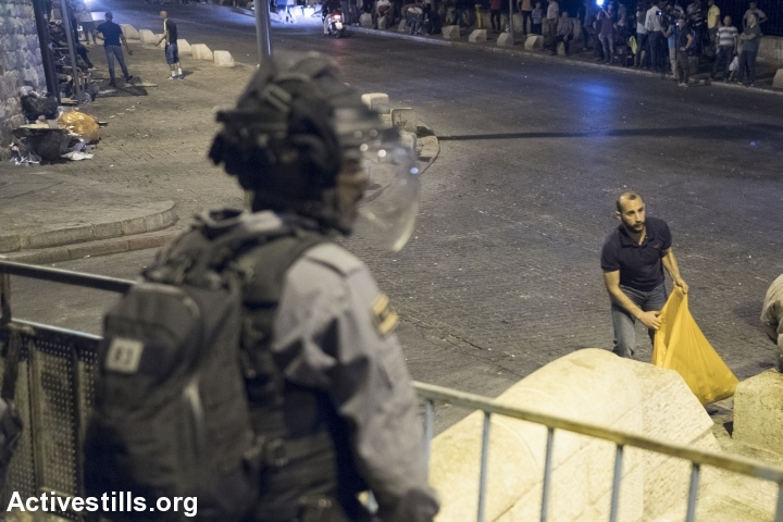 צעיר פלסטיני מנקה את הכביש בסיום תפילת הערב מחוץ לשער האריות, 26.7