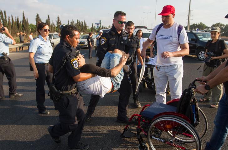 שוטרים מפנים מפגין על כיסא גלגלים. מאבק הנכים למען העלאת הקצבאות (פלאש90)