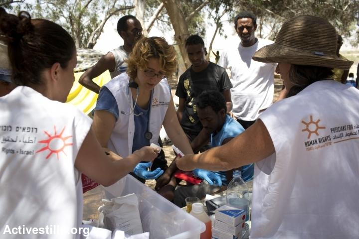 """""""הבוגדים של היום הם הגיבורים של מחר"""". מתנדבות רופאים לזכויות אדם מגישות עזרה ראשונה למבקשי מקלט על גבול ישראל-מצרים. צעדת החופש, אוגוסט 2014 (אורן זיו/אקטיבסטילס)"""