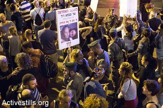 שוטר מול מפגינה על רחוב קפלן בתל אביב, הפגנת משפחות ילדי תימן (קרן מנור / אקטיבסטיילס)