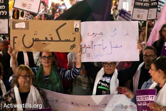 """מאות נשים ערביות ויהודיות צעדו בחיפה לציות יום המאבק באלימות נגד נשים. בשלט מימין: """"אין כבוד ברצח בשם הכבוד. תפסיקו!"""" בשלט משמאל: """"לא תשתיקו אותנו"""". 24 בנובמבר 2017. (צילום: מאריא זרייק / אקטיבסטילס)"""