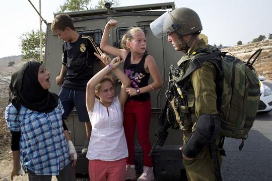 נובמבר 2012. עאהד תמימי וילדות נוספות מהכפר מנסות לחסום ג'יפ צבאי לאחר מעצר של ילד בן 15 במהלך הפגנה בנבי סאלח (אקטיבטילס)