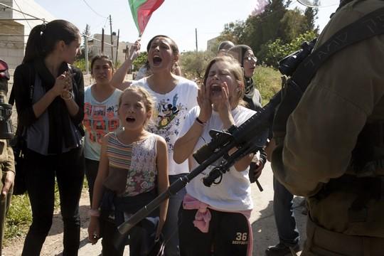 ילדות ונשים פלסטיניות, בהן עאהד תמימי, עומדות מול החיילים במהלך ההפגנה השבועית בנבי סאלח. אפריל 2012 (אקטיבסטילס)