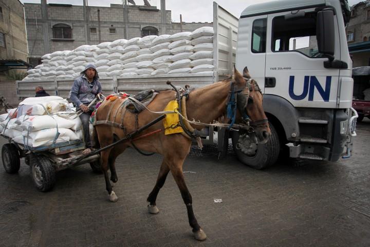 """פליטים פלסטינים אוספים חבילות סיוע במרכז חלוקת מזון של האו""""ם בח'אן יונס בדרום רצועת עזה, 28 בינואר 2018. (צילום: עבד רחים חטיב / Flash90)"""