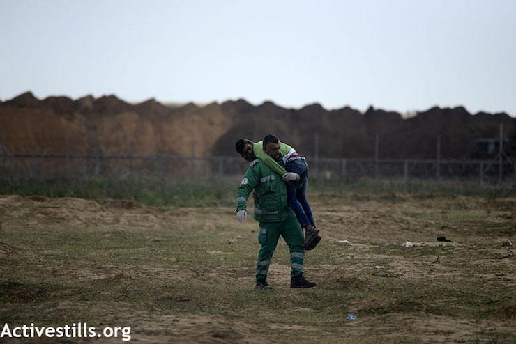 חובש מפנה מפגין פצוע מאזור הגדר במהלך צעדת השיבה הגדולה, גבול עזה, 30 במרץ 2018 (מוחמד זאנון / פלאש 90)