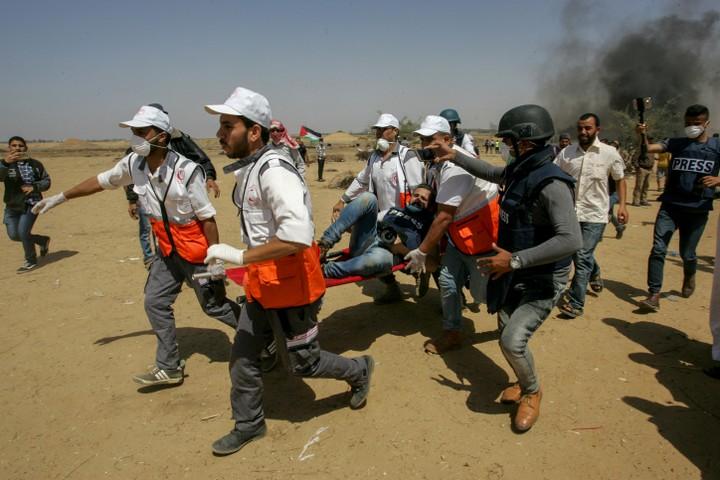 חובשים נושאים עיתונאי שנפצע במהלך הפגנות השיבה בגבול עזה. (עבד רחים ח'טיב / פלאש90