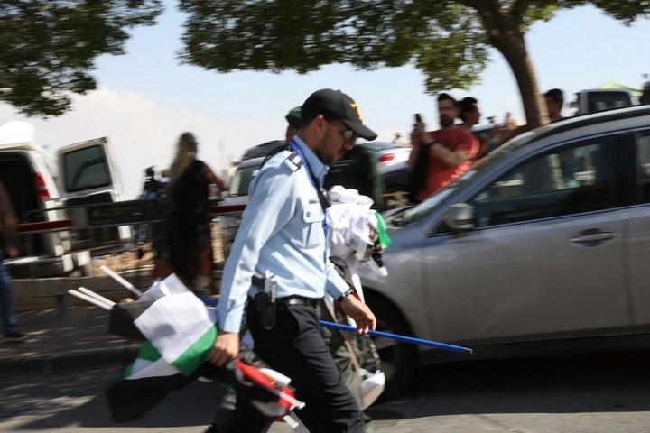 """הפגנה נגד העברת שגרירות ארה""""ב לירושלים. שוטר אוחז בדגלי פלסטין שהוחרמו באלימות מידי המפגינים. (אורן זיו / אקטיבסטילס)"""