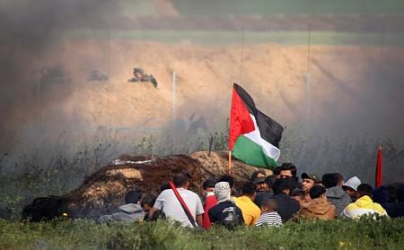 מפגינים בעזה מול הצלפים הישראלים מעבר לגדר. (צילום: עבד רחים ח'טיב/פלש90)