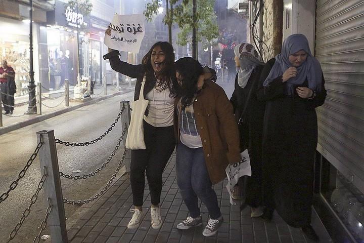"""מפגינות נמלטות מאימת רימוני הגז וההלם. הפגנה ברמאללה בקריאה להסרת הסנקציות מעל עזה. (צילום באדיבות העמוד הפלסטיני """"הסירו את הסנקציות"""")"""