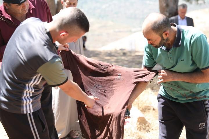 צעירים מנבי סאלח מציגים את חולצתו המחוררת של עז א-דין תמימי שנורה למות על ידי חיילים. 6 ביוני 2018 (אורן זיו / אקטיבסטילס)