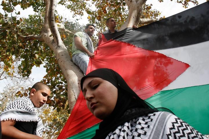 אשה נושאת דגל פלסטיני בהפגנת יום האדמה ביפו. הפלסטינים התפתחו כאן נגד הרצון הישראל (צילום: רוני שיצר/פלאש90)